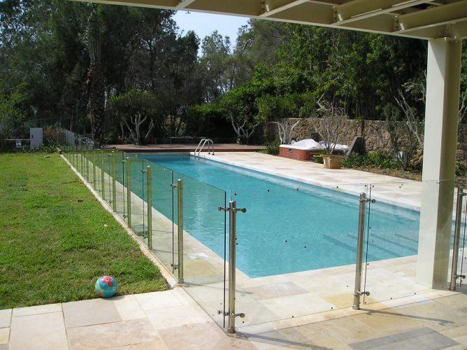 בריכת שחייה בחצר מגורים בשילוב מעקה זכוכית דגם ספיידר