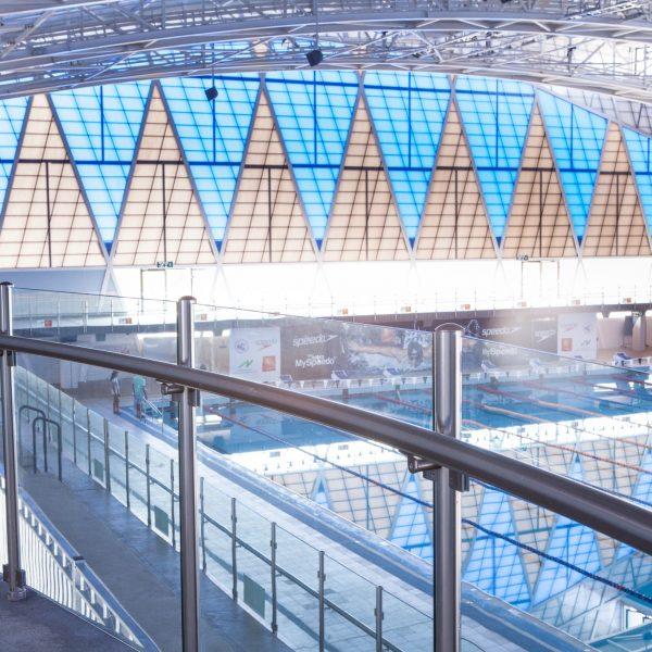 מעקה זכוכית מעוקל דגם קלאסיק עשוי אלומיניום או נירוסטה עם פרופיל עגול בבריכת שחייה